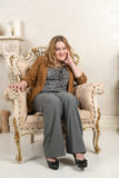 Portrait of a blonde woman in a suede jacket on a chair near the fireplace Stock Photo