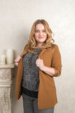 Portrait of a blonde woman in a suede jacket on near the fireplace Royalty Free Stock Photography