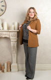 Portrait of a blonde woman in a suede jacket on near the fireplace Stock Images