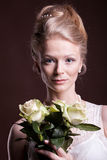 Portrait of blonde woman in victorian dress with roses in hands Royalty Free Stock Photo