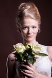 Portrait of blonde woman in victorian dress with roses in hands Stock Image
