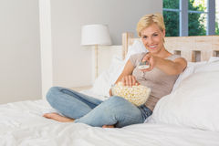 Portrait blonde woman watiching TV and eating pop corn Stock Photos