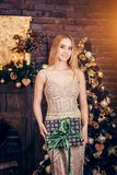 Portrait of blonde woman wearing Golden dress holding gift box on the background of Christmas decorations. Holidays, celebration stock photography