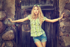Portrait of Blonde Woman at the Wooden Door Royalty Free Stock Photography