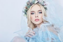 Portrait of a blonde woman with a wreath on her head and a blue delicate light transparent dress. Big blue eyes and beautiful skin stock photos