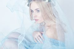 Portrait of a blonde woman with a wreath on her head and a blue delicate light transparent dress. Big blue eyes and beautiful skin