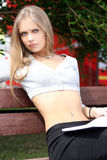 Portrait of blonde young woman sitting on the bench Stock Images