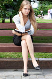 Portrait of blonde young woman sitting on the bench Royalty Free Stock Image