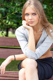 Portrait of blonde young woman sitting on the bench Royalty Free Stock Photos