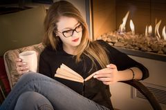 Portrait of a young blonde woman wearing eyeglasses, reading a b royalty free stock photography