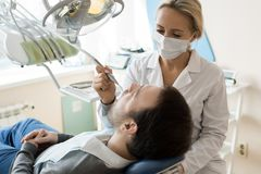 Young Female Dentist Treating Patient. Portrait of blonde young women treating teeth of relaxed men sitting in dental chair in modern clinic stock photo