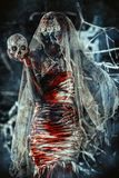 Scary bride with skull. Portrait of a bloody dead bride woman. Zombie bride. Halloween. Horror Stock Image