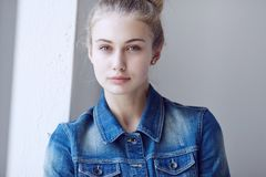 Blond female dressed in a denim jacket. Portrait of a blue eyed blond female dressed in a denim jacket Stock Image