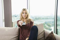 Portrait of blue eyed woman watching television on sofa at home Royalty Free Stock Images