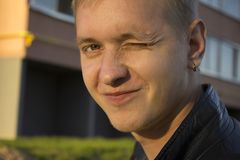 Portrait of a blue-eyed young guy blonde European man with freckles of appearance smiling and winking Stock Photos