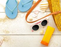 Blue flipflops, sunblock, and sunglasses on white wooden table. Portrait of blue flipflops, sunblock, and sunglasses on white wooden table with space Royalty Free Stock Photos