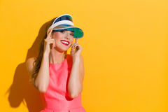 Portrait In Blue Sun Visor Cap. Smiling young woman in pink dress and sun visor posing against yellow background Royalty Free Stock Photography