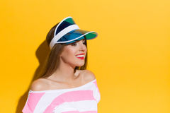 Portrait In Blue Sun Visor. Smiling young woman in pink striped shirt posing in blue sun visor and looking away. Head and shoulders studio shot on yellow Royalty Free Stock Photo