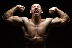 Portrait of a bodybuilder who cries. Portrait of a bodybuilder with muscles that screams strongly with his mouth open on a black background Stock Photos