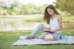Woman read book at summer park. Portrait of bohemian Asian beautiful woman read text book and sit on mat at field near pond. Outdoor education lifestyle concept Royalty Free Stock Images