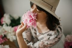 Portrait of boho girl smelling peony at pink and white peonies on rustic wooden floor. Stylish hipster woman in bohemian dress royalty free stock photos