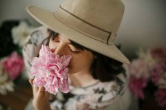 Portrait of boho girl smelling pink peony at pink and white peonies on rustic wooden floor. Stylish hipster woman in bohemian royalty free stock photos