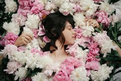 Portrait of boho woman with natural makeup lying in peonies. Creative floral photo. Aroma and spa concept. International Womens stock image