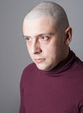 Portrait of a bold man. Portrait of a head-shaved man wearing tight sweater royalty free stock image