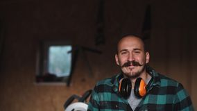 Portrait of a bold worker carpenter with vintage moustache in work clothes in front of workbench tools