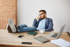 Portrait of bored adult caucasian unshaven male company manager in glasses and blue suit sitting with legs on table with. Tired and unhappy face expression royalty free stock photo