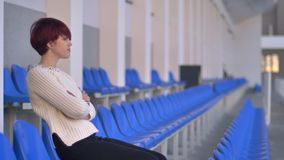 Portrait of bored beautiful pink-haired girl sitting on stadium and waiting for something with arms crossed. Portrait of bored beautiful pink-haired girl stock video footage