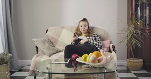 Portrait of bored Caucasian teenage girl sitting on couch and switching channels. Cute teenager watching TV at home on