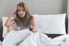 Sad young woman sitting on bed with boredom. Portrait of bored girl watching TV in bedroom. She is holding remote controller. Copy space in right side Royalty Free Stock Photo