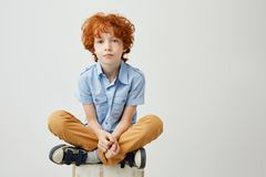 Portrait of bored little kid with red hair and freckles sitting on box with unhappy expression, being tired of waiting. His mom wrom work Stock Photos