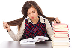 Portrait of  bored schoolgirl doing his homework at desk Royalty Free Stock Photography