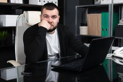 Portrait of young man propping up back of his throat with laptop in business office royalty free stock photos