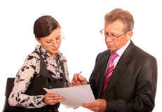 Portrait of boss and secretary. Chief signs document, which secretary has submitted to it, it is isolated on white background Stock Photo