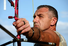 Portrait of bowman aiming with bow and arrow Royalty Free Stock Photography