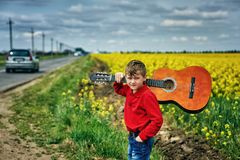 Portrait of a boy with an acoustic guitar in a yellow field. A boy with a guitar on the nature of the concept of children`s music education royalty free stock photo
