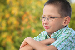Portrait of boy with arms across in fall park Royalty Free Stock Photos