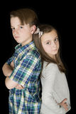 Portrait of boy with arms folded and girl with hands on her hips Royalty Free Stock Image