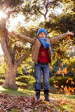 Portrait of boy with arms outstretched at park during autumn Royalty Free Stock Photo