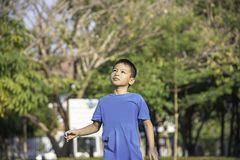 Portrait of a boy Asia laughing and smiling happily Background blurry trees in park.  royalty free stock photo