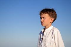 Portrait of boy on background of blue sky Stock Photo