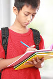 Portrait of boy with backpack writing Stock Photography