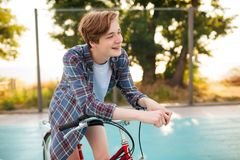 Boy with blond hair in casual shirt standing with red bicycle on basketball court in park. Young man joyfully looking. Portrait of boy with blond hair in casual Stock Images