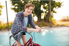 Boy with blond hair in casual shirt standing with red bicycle on basketball court in park. Young smiling man happily. Portrait of boy with blond hair in casual Royalty Free Stock Image