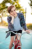 Boy with blond hair in shorts and casual shirt standing with red bicycle on basketball court in park. Young man dreamily. Portrait of boy with blond hair in Stock Image