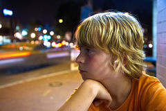 Portrait of a boy with blonde hair outside on the street at night Stock Photos