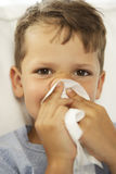 Portrait of a boy blowing nose on a handkerchief Royalty Free Stock Photography